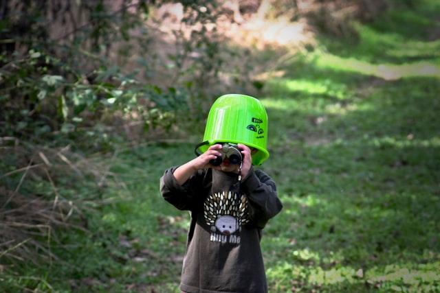 enfant portant des jumelles dans la nature