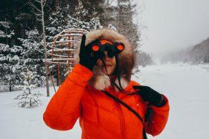femme utilisant une paire de jumelles noires aux optiques rouges